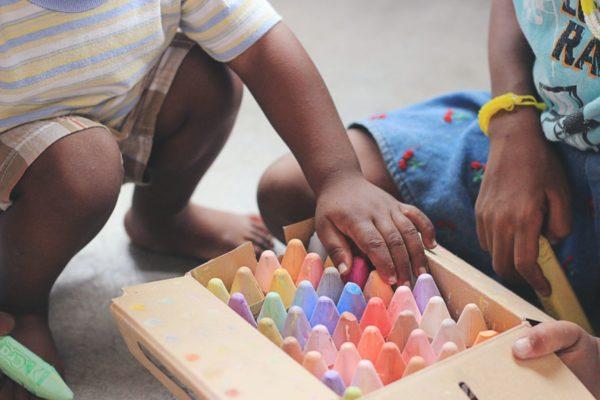enfant accroupi devant une caisse de grosse craie de couleurs