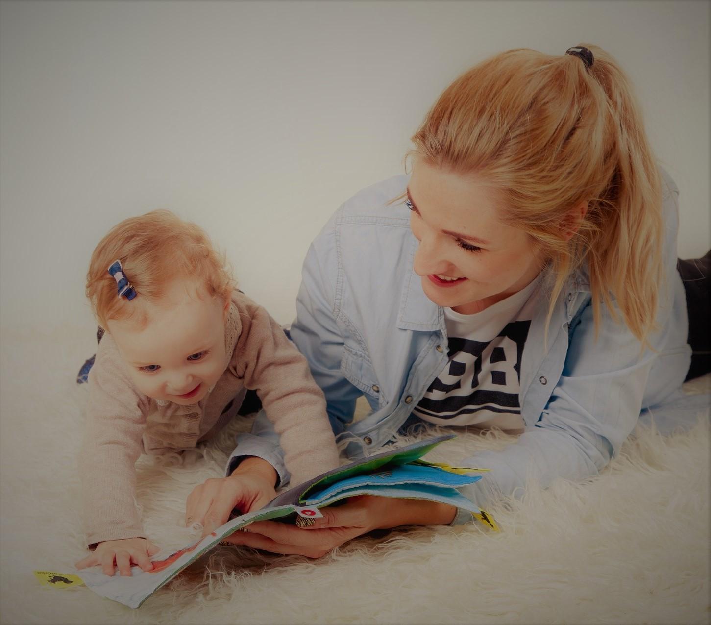 mère et son enfant en train de lire un livre allongés